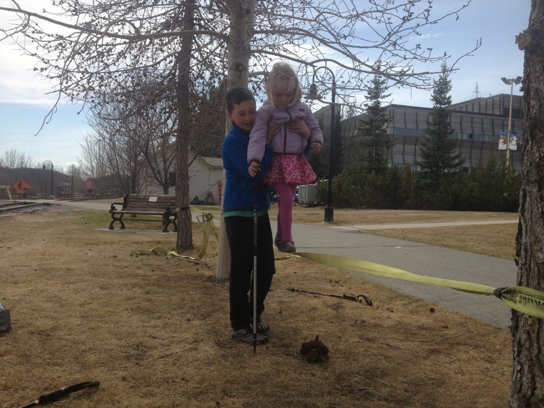 Ben guiding one of the preschool students through the slackline.